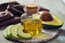 bottle of avocado essential oil with fresh avocado fruit closeup
